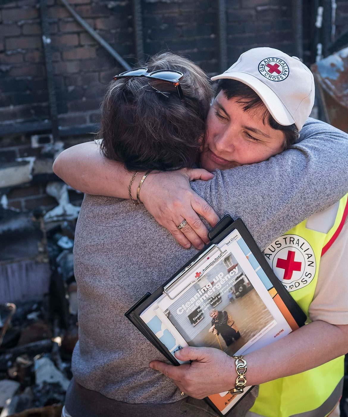 Red cross worker hugging woman