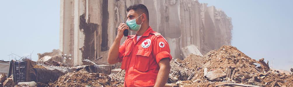 LRC volunteer stands against backdrop of destroyed port in Beirut