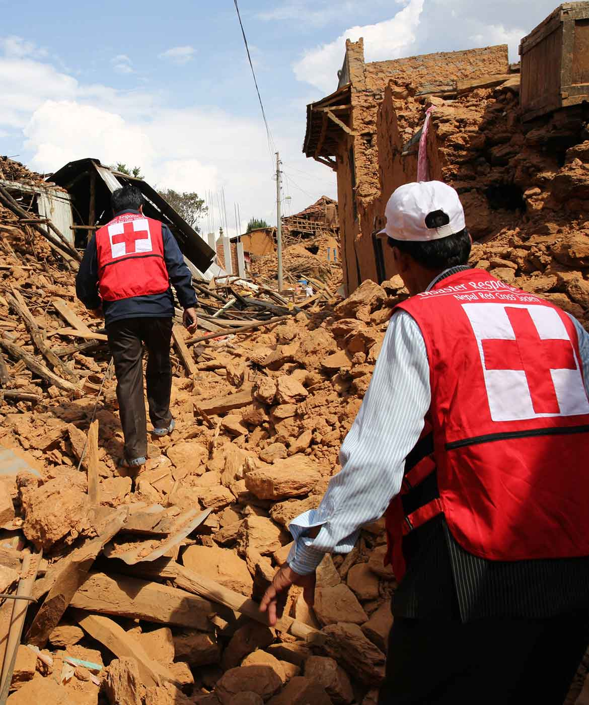 Red Cross volunteers walk through buildings destroyed by the Nepal earthquake