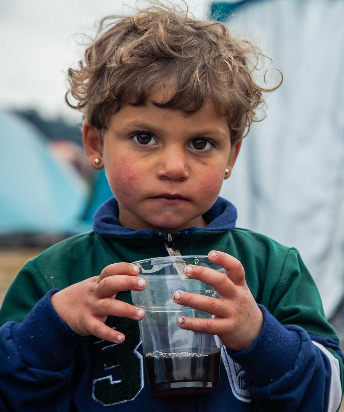 Three year old Lama warms her fingers with a cup of tea. Her family fled their home in Syria but were stranded at the border in Greece for several weeks.