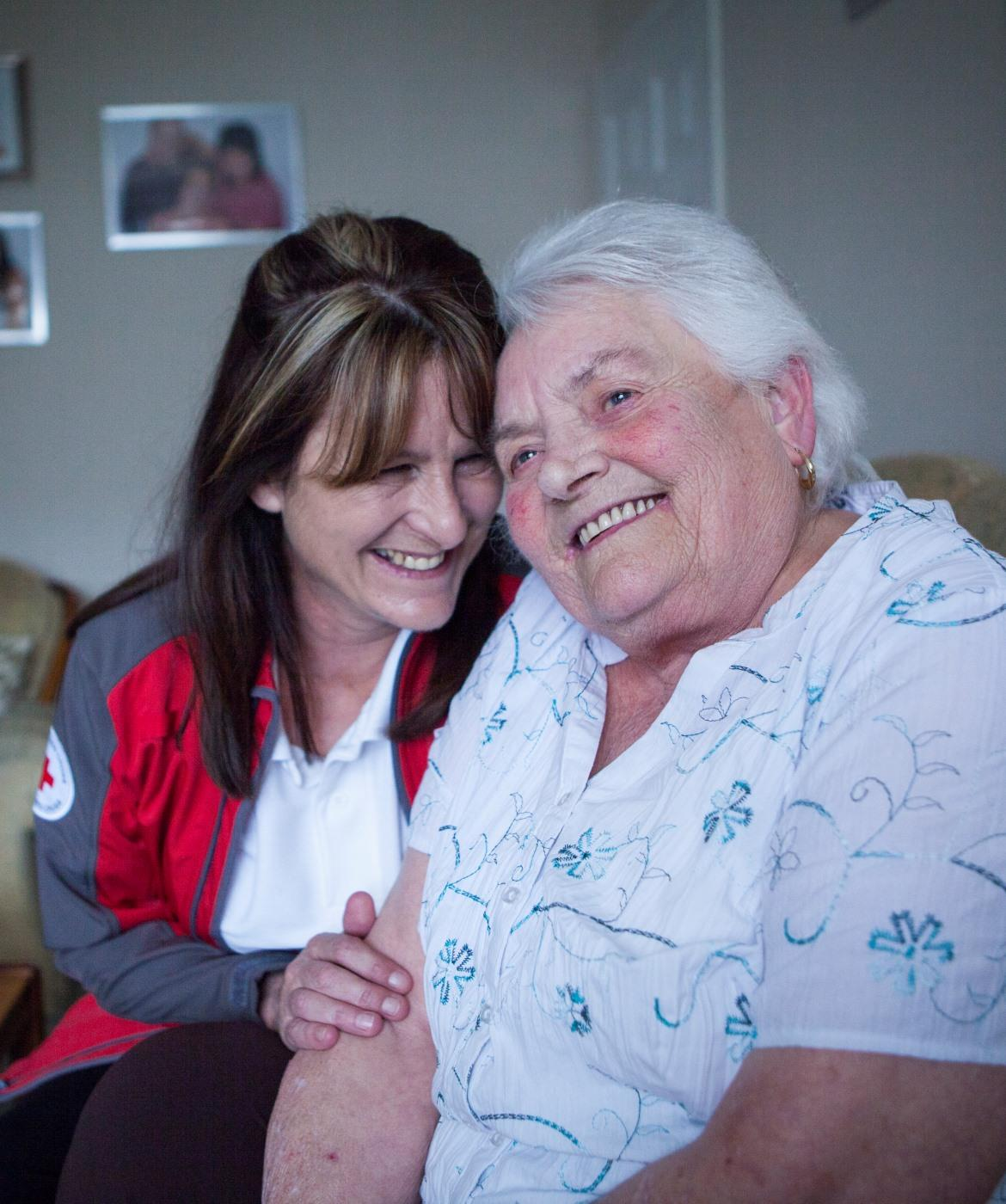 A Red Cross Volunteer sits with a woman
