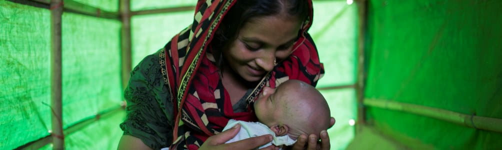 Woman holds her baby in a tent in Cox's Bazar