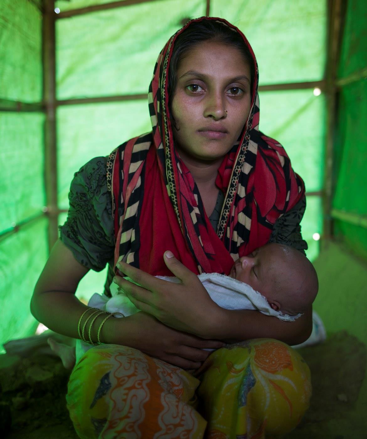 A woman holds her baby in a tent in Cox's Bazar