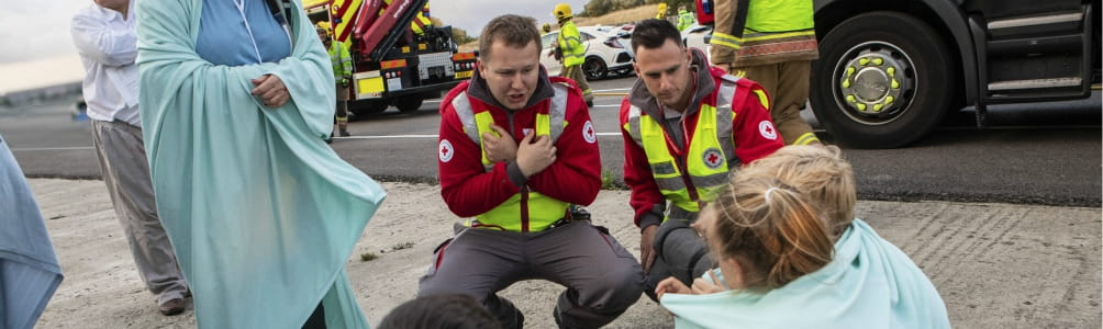 Specially trained British Red Cross volunteers treat a woman with first aid after a car crash