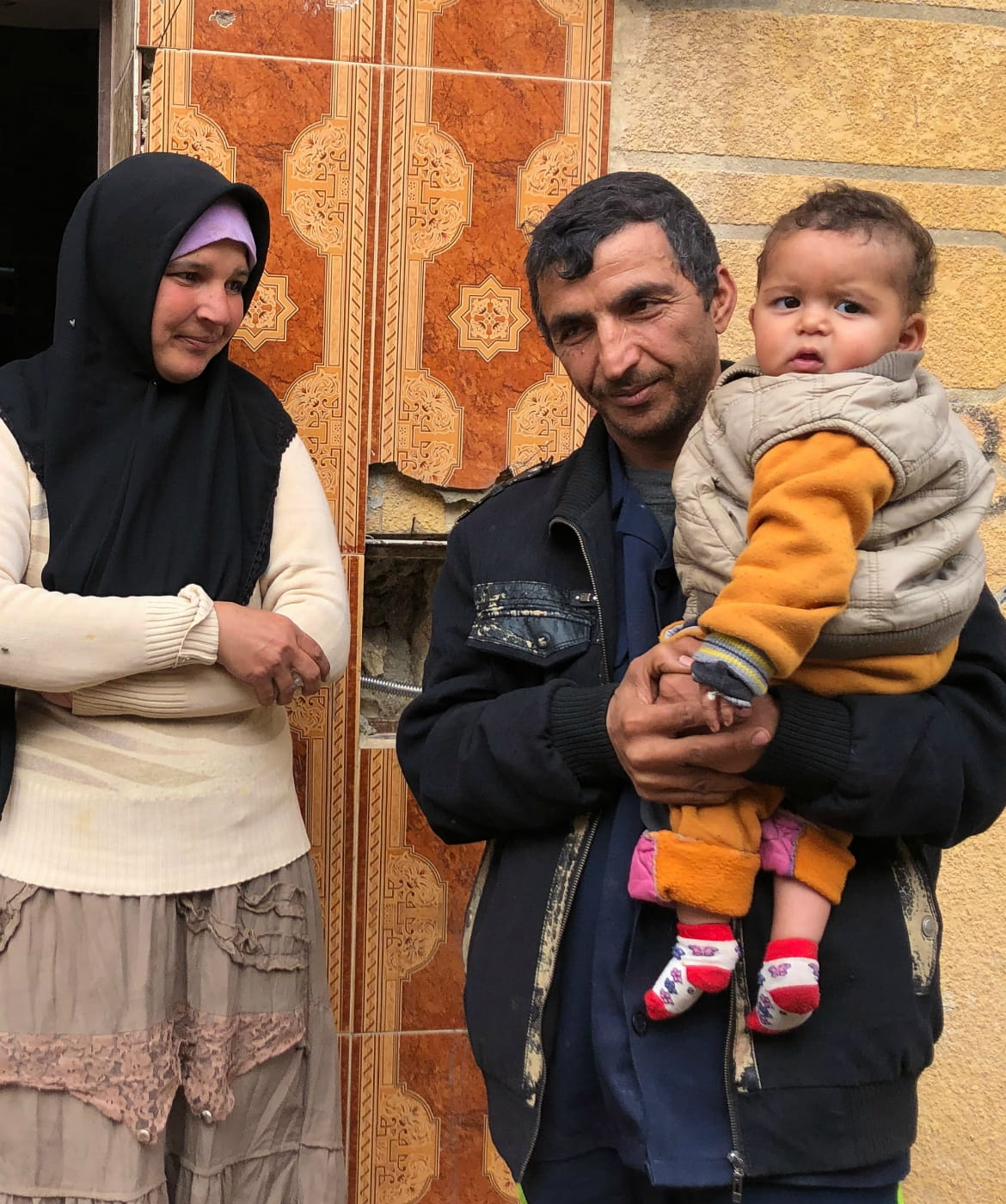Sobhi and his wife Fatoum, with their one-year-old son, Sharif, outside their small home in Aleppo.
