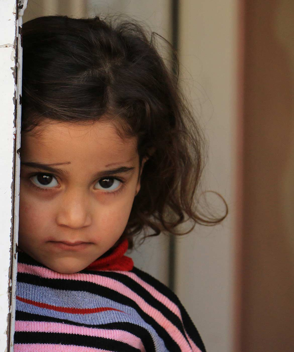 Young Syrian girl peers from being a door frame