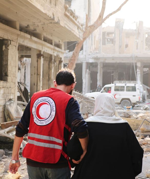 Red Crescent worker assisting Syrian woman