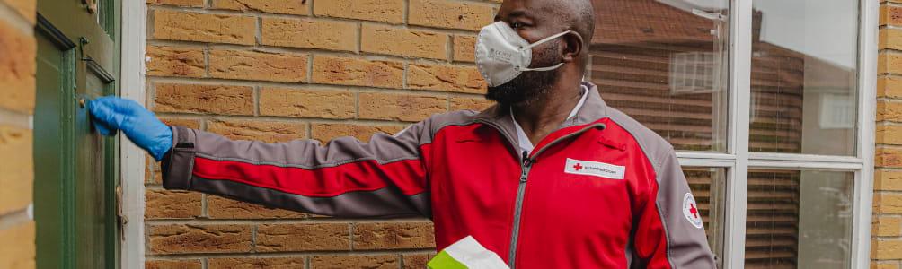 Emergency Response volunteer, Emmanuel, knocking on the door to deliver a prescription