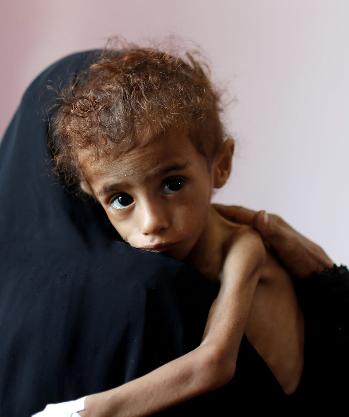 Young child in Yemen being held by mother