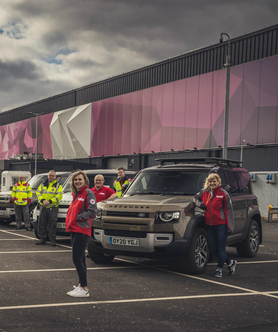 Red Cross personnel pose with Land Rover vehicles